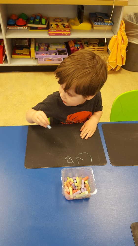 Practicing spelling his name with chalk at preschool.